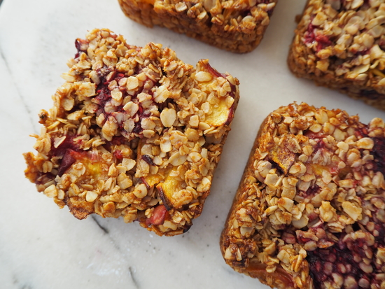 Close up of 4 square peach melba flapjacks on a white marble background