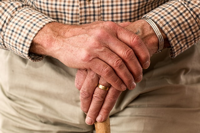close up of an old mans hands holding thee top of a walking stikc so that you can barely see it