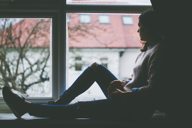 woman sat in a window looking out. the image is dull colours, very depressing and it suggests she is suffering with post natal anxiety